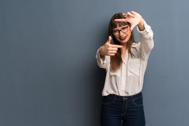 Женщина с очки над синей стены, фокусировка лица. обрамление символ