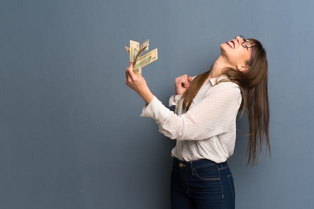 たくさんのお金を取って青い壁の上の眼鏡を掛けた女性