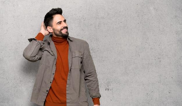Красивый мужчина с бородой, думая, идея почесывая голову над текстурированной стеной