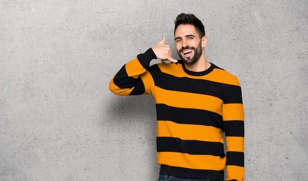 電話のジェスチャーを作る縞模様のセーターを持つハンサムな男は。織り目加工の壁を越えて私にサインバックを呼び出します