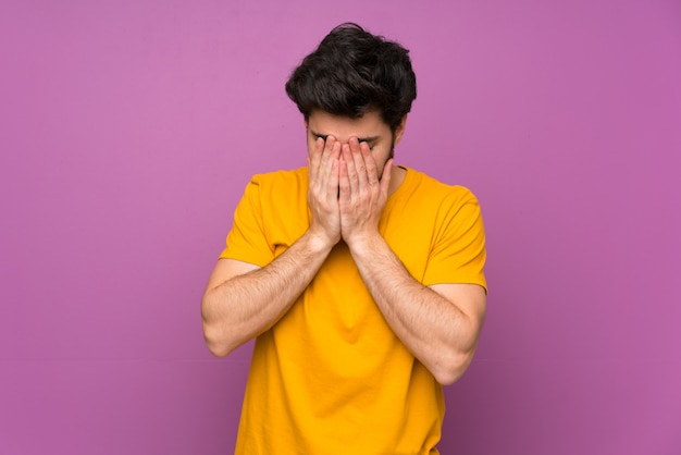 Красивый над изолированной фиолетовой стеной с усталым и больным выражением