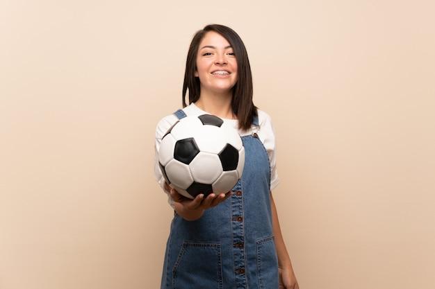 孤立したサッカーボールを保持している上の若いメキシコ人女性