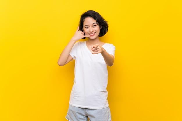 電話のジェスチャーを作ると前方を向く孤立した黄色の壁の上のアジアの若い女性