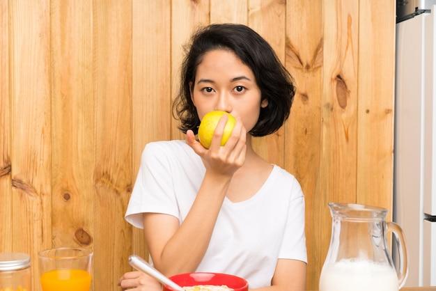 アジアの若い女性、朝食をとり、リンゴと