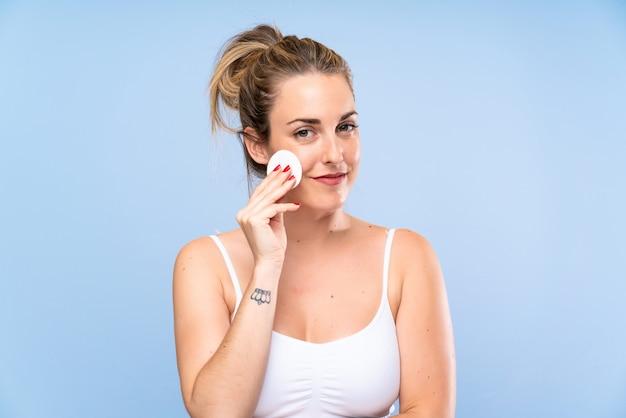 Молодая блондинка снимает макияж с лица с помощью ватного диска