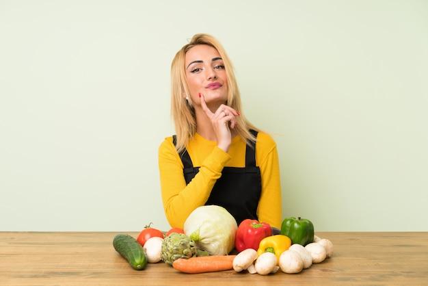 Молодая блондинка с большим количеством овощей, думая, идея