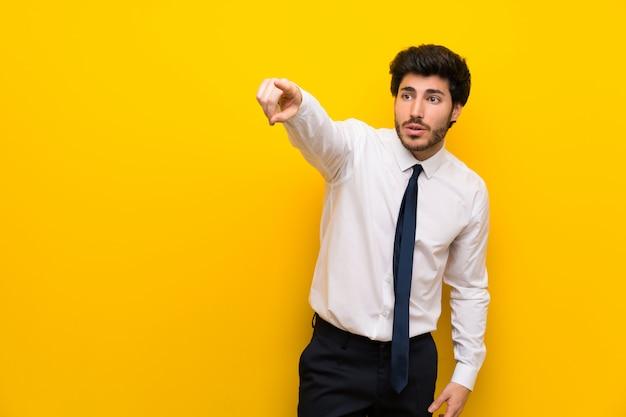 Бизнесмен на изолированном желтом фоне, указывая прочь