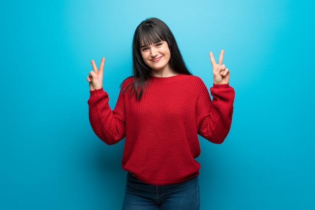 笑みを浮かべて、両手で勝利のサインを示す青い壁に赤いセーターを持つ女性