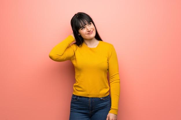 頭を悩ませながらアイデアを考えてピンクの壁の上の黄色いセーターを持つ女性