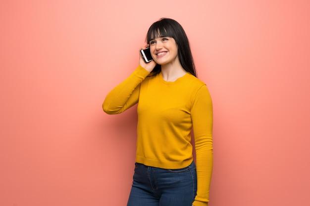 携帯電話との会話を維持するピンクの壁の上の黄色いセーターを持つ女性