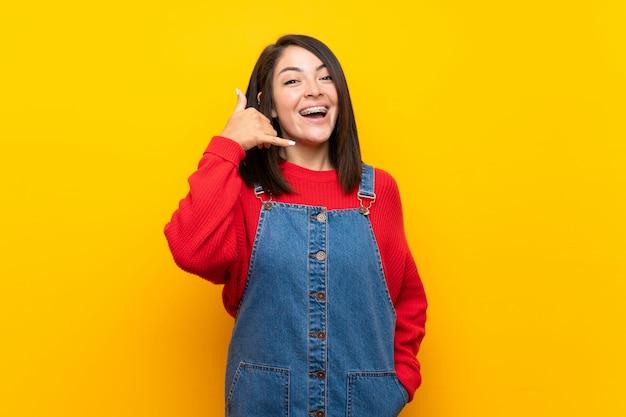 電話のジェスチャーを作る黄色の壁の上のオーバーオールを持つ若いメキシコ人女性。私にバックサインイン