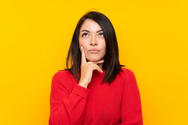 アイデアを考えて黄色の壁の上の赤いセーターを持つ若いメキシコ人女性