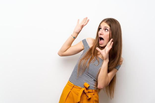 緊張と怖い孤立した白い壁の上の長い髪を持つ若い女