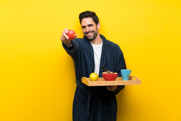 Красивый мужчина в пижаме над изолированной желтой стеной