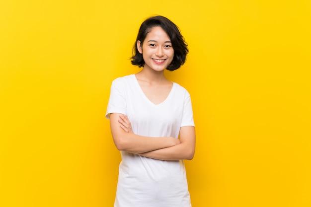 腕を組んで正面位置に保つ孤立した黄色の壁の上のアジアの若い女性