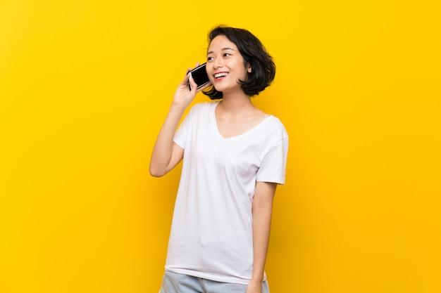 Азиатская молодая женщина над изолированной желтой стеной, ведение разговора с мобильным телефоном