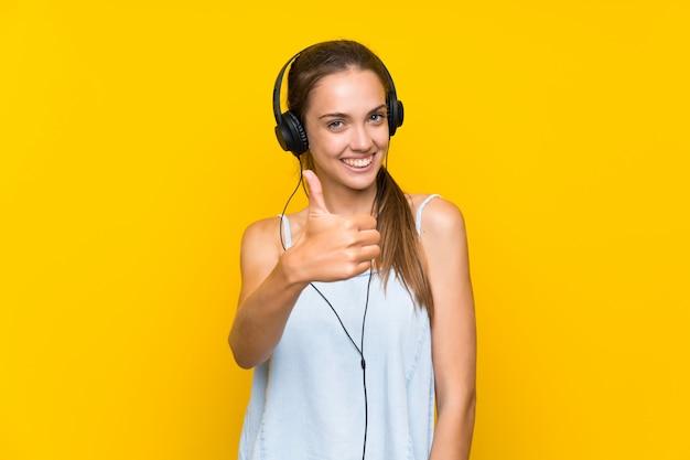 Музыка молодой женщины слушая над изолированной желтой стеной с большими пальцами руки вверх потому что что-то хорошее случилось