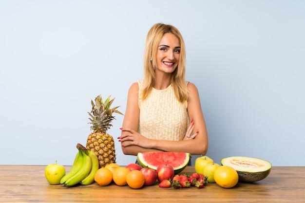 笑ってたくさんの果物を持つ若いブロンドの女性