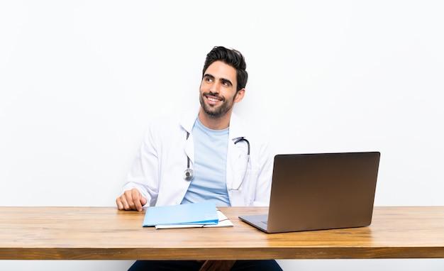 笑って見上げる孤立した壁の上の彼のラップトップを持つ若い医者男