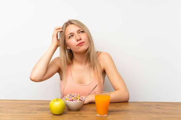 疑問を持つと混乱の表情で朝食を持つ若いブロンドの女性