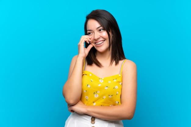 笑って孤立した青い背景上の若いメキシコ人女性