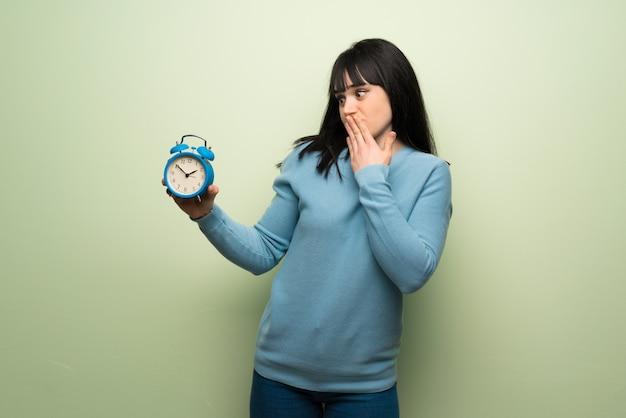 ビンテージの目覚まし時計を保持している緑の壁を越えて若い女性