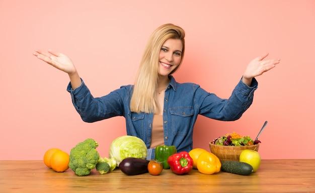 多くの野菜を提示し、手で来ることを勧めている若いブロンドの女性