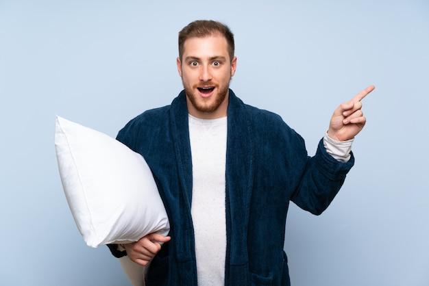 Блондинка в пижаме над синей стеной удивлена и указывает пальцем в сторону