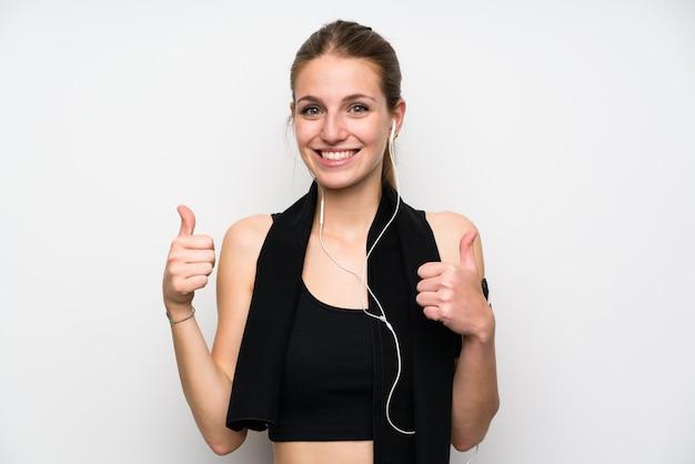 Молодая женщина спорта над изолированной белой предпосылкой давая жест больших пальцев руки вверх