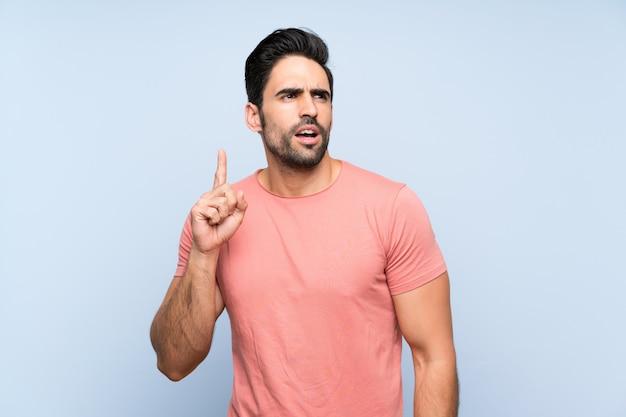 指を上向きのアイデアを考えて孤立した青い背景上のピンクのシャツでハンサムな若い男