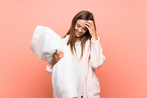笑ってピンクの壁の上のドレッシングガウンの若い女性