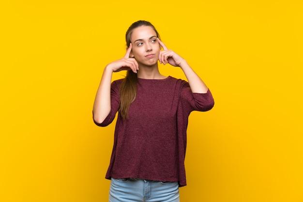 疑問を持つと考えて分離の黄色の背景上の若い女性