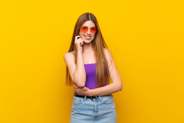 メガネと笑顔で孤立した黄色の背景上の若い女性