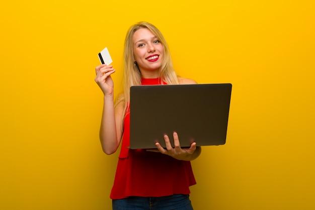 ノートパソコンとクレジットカードで黄色の壁を越えて赤いドレスを持つ若い女の子
