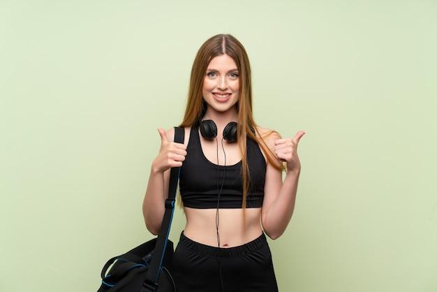 親指を立てるジェスチャーを与える若いスポーツ女性