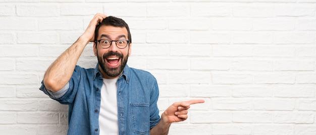 Красивый мужчина с бородой над белой кирпичной стеной удивлен и указывая пальцем в сторону
