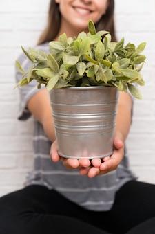植木鉢を取って家の若い女性