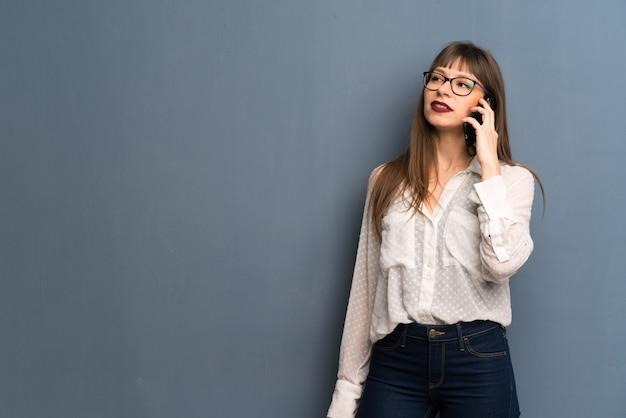 携帯電話との会話を維持するメガネの女