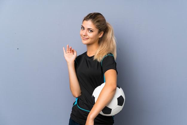 Белокурая девушка-подросток футболиста над серой стеной