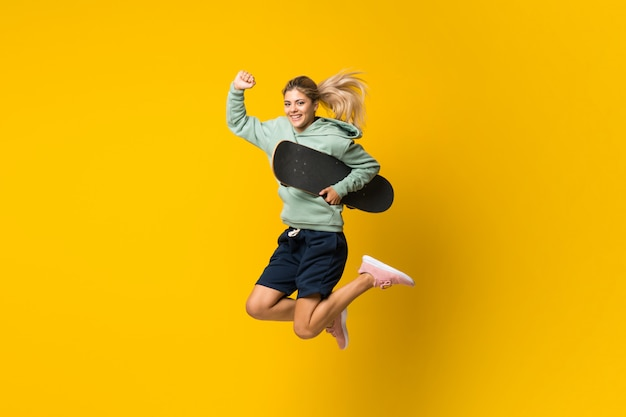 孤立した黄色を飛び越えてブロンドのティーンエイジャーのスケーターの女の子