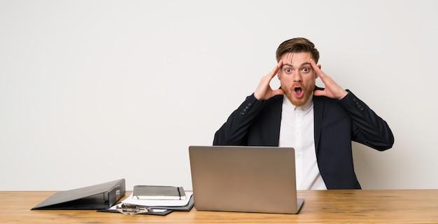 Бизнесмен в офисе с выражением удивления