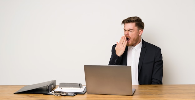Бизнесмен в офисе зевая и прикрывая широко открытый рот рукой
