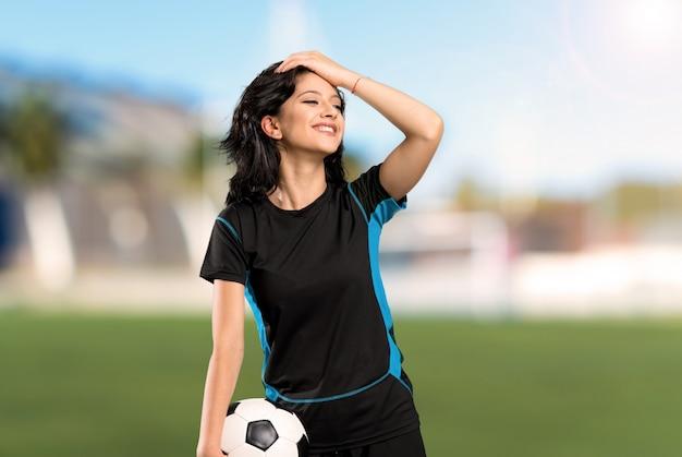 若いサッカー選手の女性は何かを実現し、屋外で解決策を目指しています