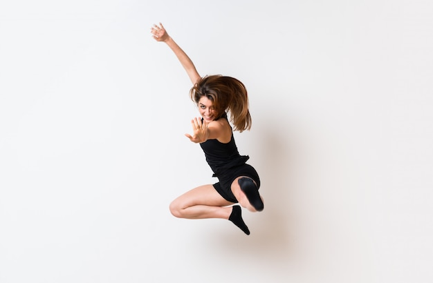 Молодая девушка танца изолировала белую стену