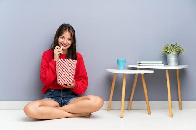 Молодая женщина сидит на полу и держит попкорн