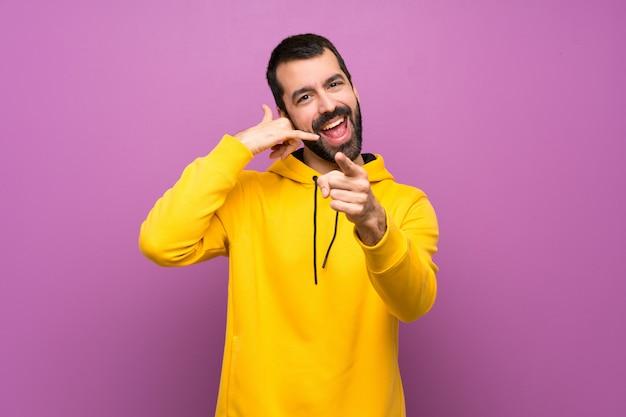 電話のジェスチャーを作ると前方を向く黄色のスウェットシャツを持つハンサムな男