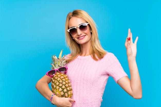サングラスとパイナップルを保持している若い女性