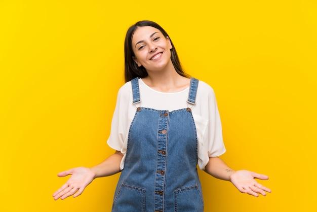 黄色の笑顔で分離されたダンガリーの若い女性