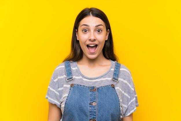 驚きの表情で黄色に分離されたダンガリーの若い女性