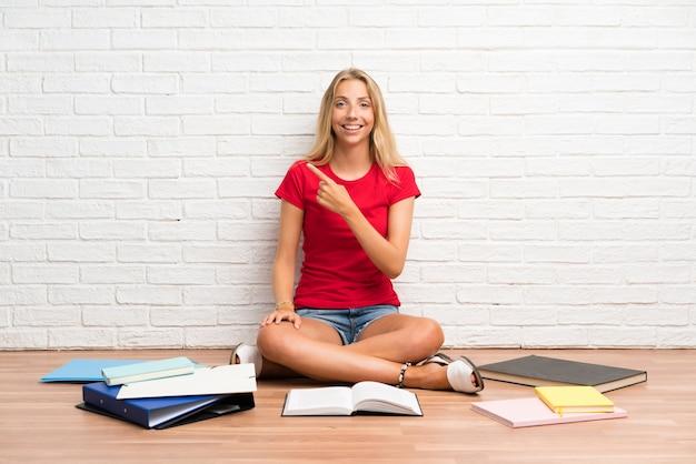 側に指を指して床に多くの本を持つ若い金髪学生少女
